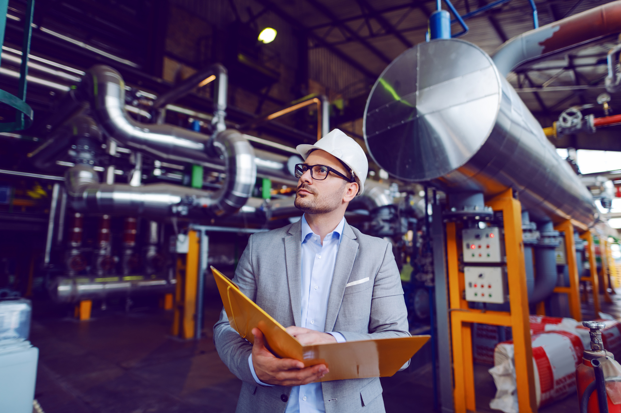 A man inspecting piping systems in a building