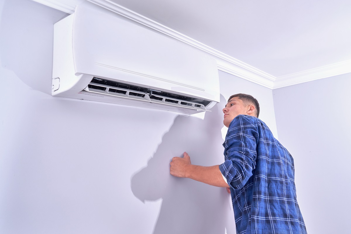 A man inspects the air conditioner at home, checks if it works