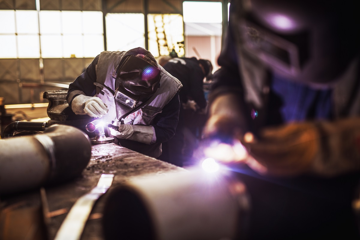 Close up of a male fabric worker cutting metal pipe with an electric grinder in workshop.