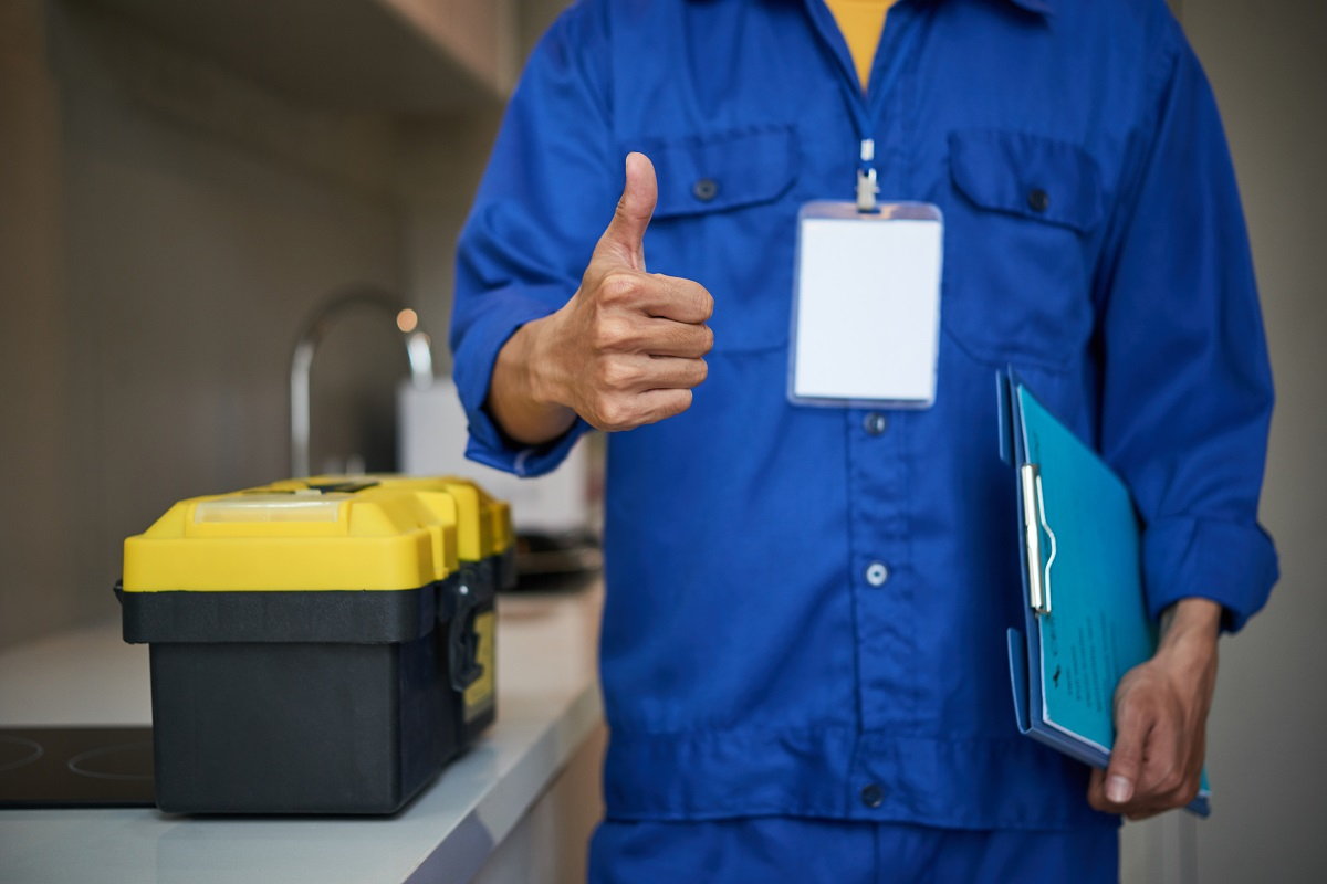 Cropped image of repaiman with tool box showing thumbs-up